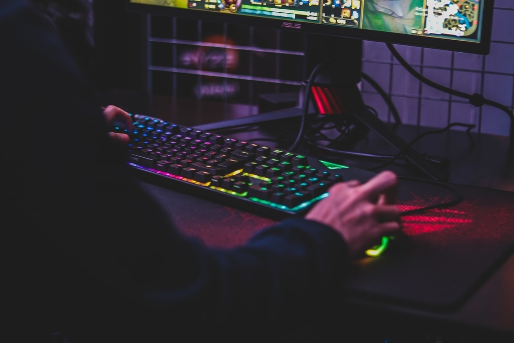 RGB gaming keyboard infront of a screen